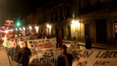 Padres de normalistas de Michoacán marchan en la vispera de navidad